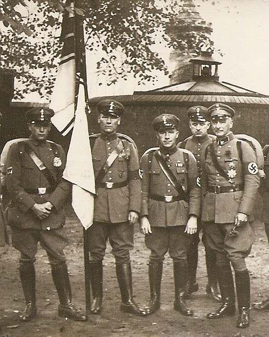 """Aufmarsch des von den Nazis gleichgeschalteten """"Stahlhelms, Bund der Frontsoldaten"""". Bei den abgebildeten Personen handelt es sich um Veteranen des Ersten Weltkriegs. Ausschnitt aus einem von meiner Mutter erstellten Foto, um 1934. Ergänzende Beschreibung der Uniform von Et Mikkel: Uniform des """"Wehrstahlhelm"""". (Die abgebildeten Personen) tragen die Uniform der kaiserlichen Armee mit dem kleinen Marschgepäck (Tornister und Decke), die mit nationalsozialistischen Emblemen ergänzt wurden: Zwischen den Kokarden befindet sich der NS-Parteiadler und am linken Oberarm die Armbinde der NSDAP. Darüber wurde normalerweise das Provinz- oder Landesabzeichen der jeweiligen Einheit getragen. Auf dem rechten Oberarm wird dagegen das Abzeichen des Reichskriegerbundes getragen. Daneben wird hier auch die Reichskriegsflagge (1903–1918) geführt."""